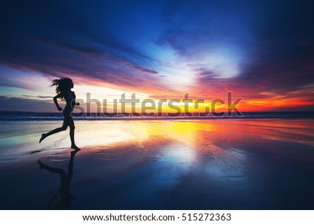 Woman running on tropical beach at sunset, sea on background