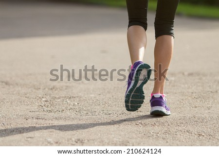 Woman running outdoors in morning - stock photo