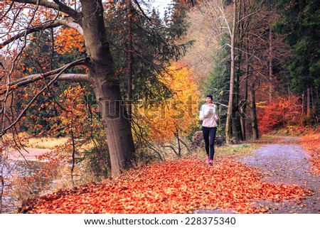 woman running through the forest by the lake - stock photo