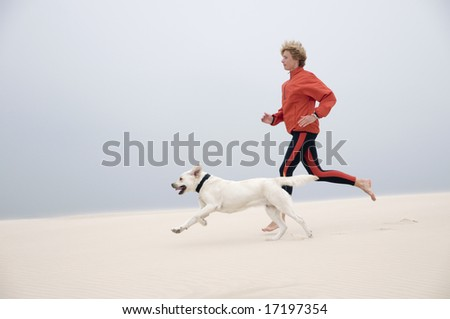 Woman running with dog on the dune - stock photo