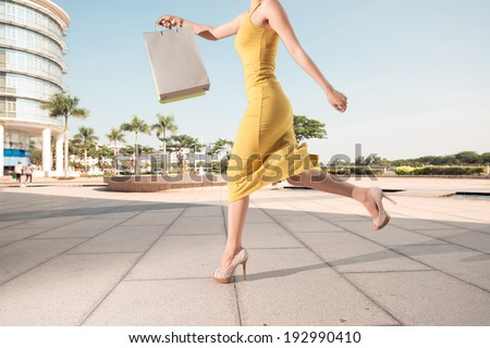 Woman running with shopping bag - stock photo