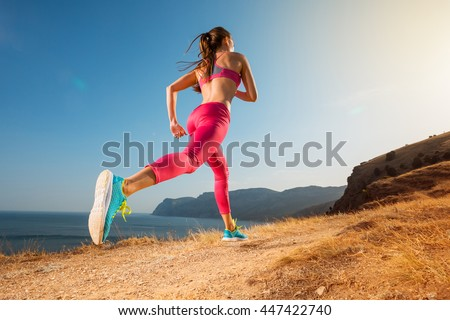 Woman running. Young girl runner jogging on a mountain trail in the beautiful landscape. Healthy sport lifestyle. Fitness and workout on outdoors. - stock photo