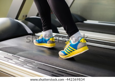 woman runs on a treadmill, exercise in the sport club - stock photo