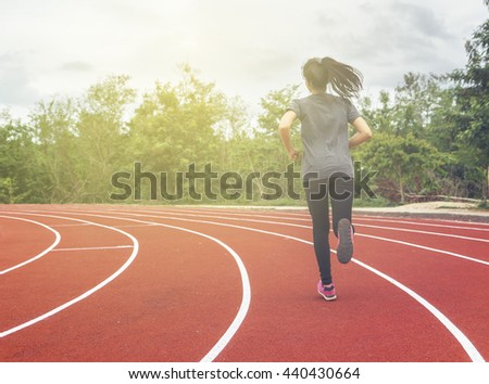 Woman runs on the track with soft light