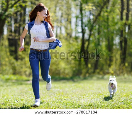 woman runs with a dog in a summer park - stock photo
