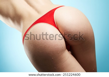 Woman's ass in red panties on blue background - stock photo