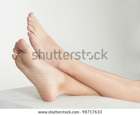 Woman's Bare Feet Crossed at the Ankles and Elevated Against a White Studio Background