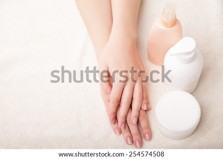 Woman's beautiful hands with care cream bottles on the white background - stock photo