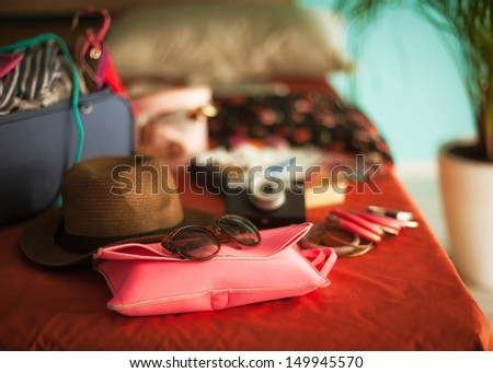 Woman's bedroom full of things ready to be taken on summer holiday. - stock photo