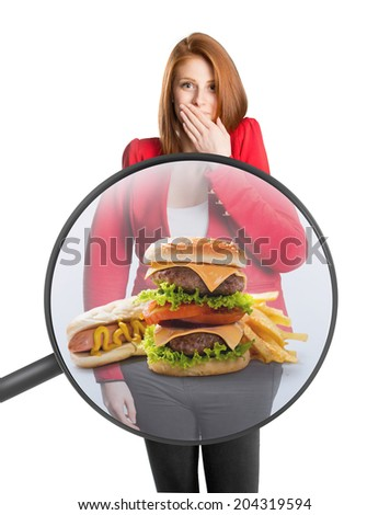 Woman's belly with food under a magnifying glass - stock photo