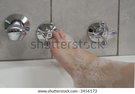 Woman's boot adjusting the hot water tap in a bubble bath