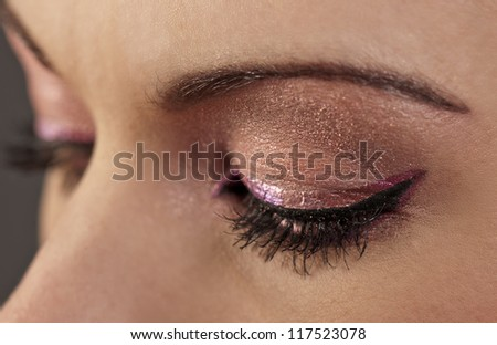 Woman's closed eyes with graphic pink and purple makeup