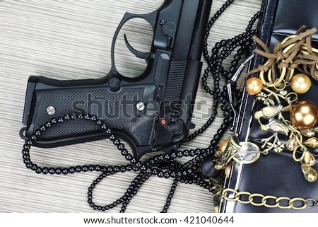 Woman's clutch with gun and accessories, Handgun and accessories falling from a woman's purse. - stock photo