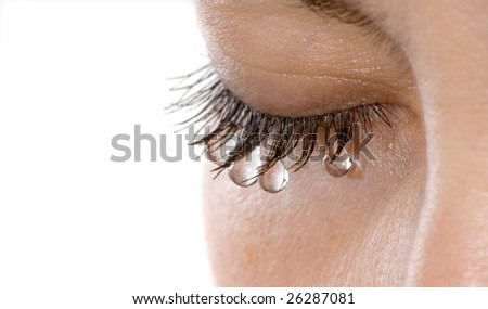 Woman's eye with several teardrops hanging on her eyelashes - isolated - stock photo