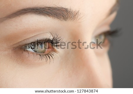 woman's eyes close-up on gray background - stock photo