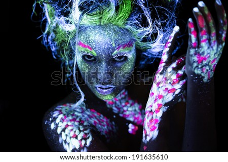 Woman's face with fluorescent body art. Black background. - stock photo