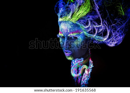 Woman's face with fluorescent bodyart. Black background. - stock photo