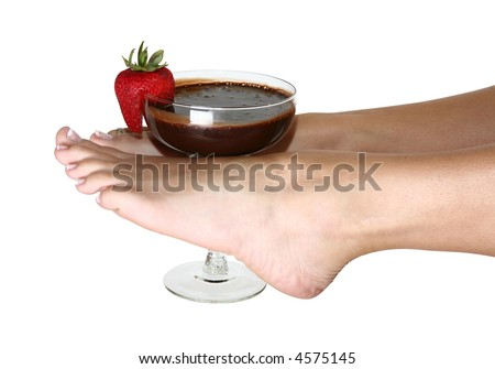 Woman's feet holding glass of chocolate sauce and strawberry.  Clipping path included. - stock photo
