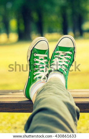 Woman's feet in a green canvas sneakers relaxing on a bench.