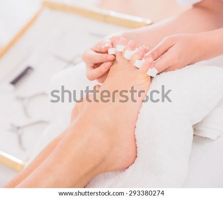 Woman's feet in pedicure toe separators at the nail salon. - stock photo