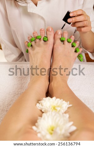 Woman's feet in pedicure toe separators at the nail salon. Beautician applying nail polish  - stock photo