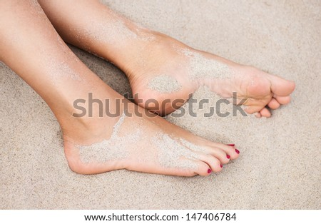 woman's feet on the sand at the beach