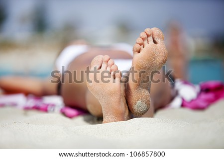 Woman's feet on the white sand. Heels of a girl sunbathing on the beach. concept of the rest and relaxation - stock photo