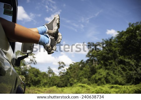 Woman's Feet Sticking Out of Car - stock photo