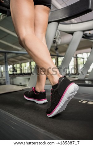 Woman's feet while walking on thread mill at gym