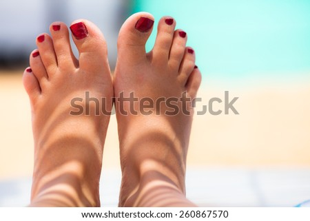 Woman's feet with red nail polish - stock photo