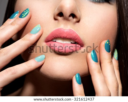 Woman's fingers with motton blue color of the nails on the face