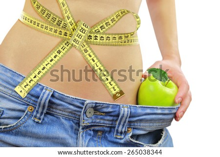 Woman's fit belly with measuring tape,apple and oversized jeans, isolated on white - stock photo