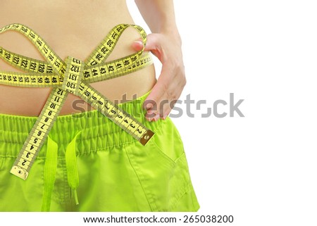 Woman's fit belly with measuring tape, isolated on white - stock photo