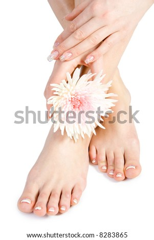Woman's foot and hand with flowers isolate on white - stock photo