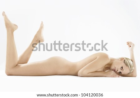 Woman's full naked body laying down on a white background.