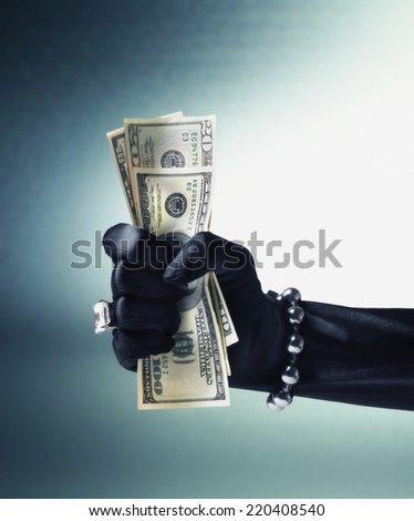 Woman's gloved and jeweled hand crushing US hundred dollar bills - stock photo