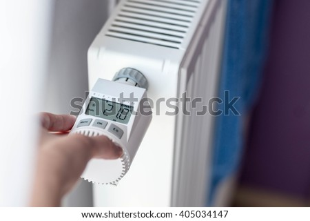 Woman's hand adjusting temperature on home wall heater