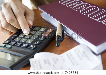 woman's hand calculating her finance - stock photo