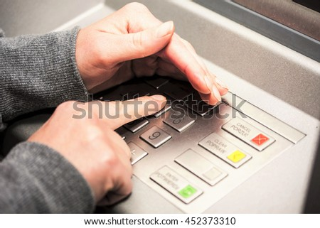 Woman's hand covers his hand when entering your PIN into an ATM