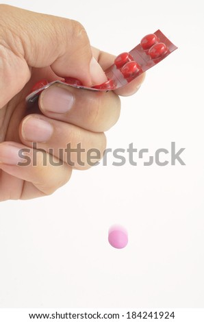 Woman's hand dispensing pill from packet