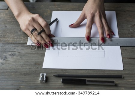 Woman's hand drawing with straightedge  - stock photo