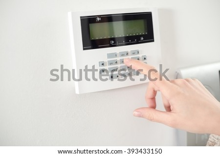 Woman's hand entering code on keypad - stock photo