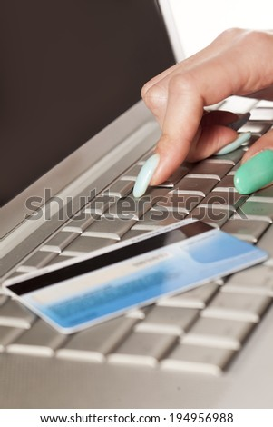 Woman's hand entering credit card information into a laptop