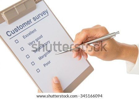 Woman's hand fills out customer survey on white - stock photo