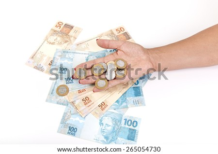 Woman's hand holding a Brazilian coin and mirrored money on white background