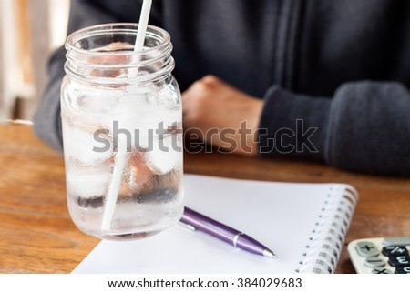 Woman's hand holding a cold glass of water, stock photo