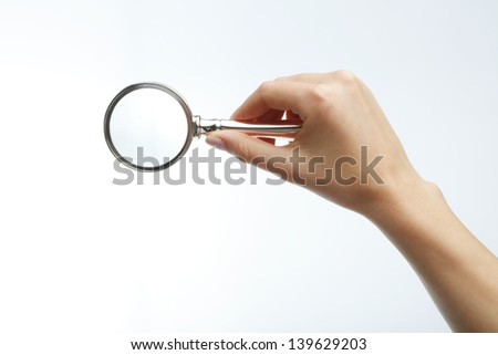 Woman's hand holding a magnifying glass. Isolated on white background.