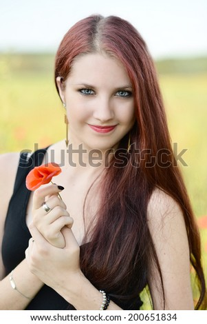 Woman's hand holding a poppy lit evening sun