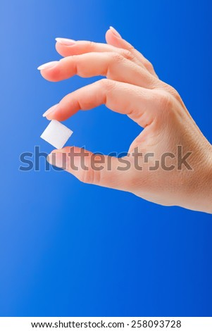 Woman's hand holding a white sugar cube on blue background - stock photo