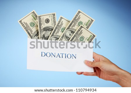 Woman's hand holding an envelope with money on blue background - stock photo